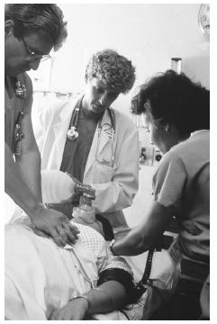 Emergency team treating heart attack patient. (Custom Medical Stock Photo. Reproduced by permission.)