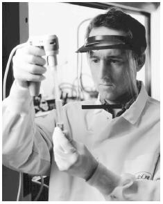 A technician performs laboratory urine drug testing. (Photograph by Edward L. Lallo. The Picture Cube. Reproduced by permission.)
