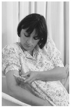 A woman with gestational diabetes injects herself with insulin daily to treat her condition. (Photograph by Mark Clarke. Science Source/Photo Researchers. Reproduced by permission.)