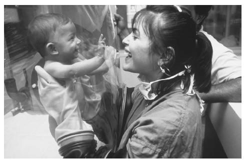 A nurse holds a baby with immunodeficiency, who must be treated in a sterile environment. (Science Source/Photo Researchers. Reproduced by permission.)