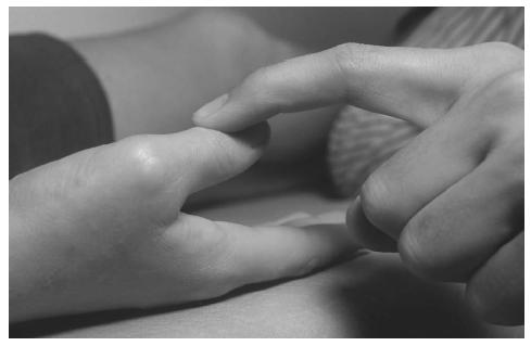 This therapist is testing the muscles of the patient's hand by pressing on the thumb. (Photograph by John Watney. Science Source/Photo Researcherso. Reproduced by permission.)