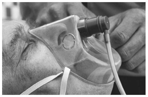 A man is given oxygen via a face mask before being transported to the hospital. (Photograph by Adam Hart-Davis. Science Source/Photo Researchers. Reproduced by permission.)