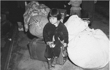 This young girl is waiting for her family to be checked into a internment camp. Courtesy of the Library of Congress.